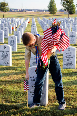 Veterans Day - Scouts: Mattison Parker, 12, of Boy Scout Troop 255 places a flag next to a headstone at the Central Texas Veterans Cemetery on Monday, Nov. 11, 2013, in honor of Veterans Day. - Jodi Perry | Herald