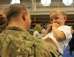 937th Route Clearance Company Homecoming: Spc. Landon Soper, 937th Route Clearance Company, 8th Engineer Battalion, 36th Engineer Brigade, holds his son, Gauge, 2, during a homecoming ceremony Monday, Nov. 4, 2013, at the West Fort Hood Physical Fitness Center. - Photo by Herald/CATRINA RAWSON