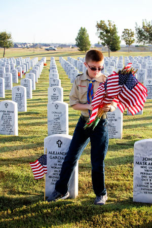 Veterans Day - Scouts: Mattison Parker, 12, of Boy Scout Troop 255 places flags on graves at the Central Texas Veterans Cemetery on Monday, Nov. 11, 2013, in honor of Veterans Day. - Jodi Perry | Herald
