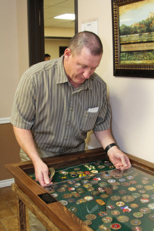 Coins (5): Dale Cowan, director of the Masters Club at North Side Baptist Church, looks at coins collected as part of the church's children's program. Cowan said the coin collection started in 2010 as a way for the children to learn more about God and their country. - Jodi Perry
