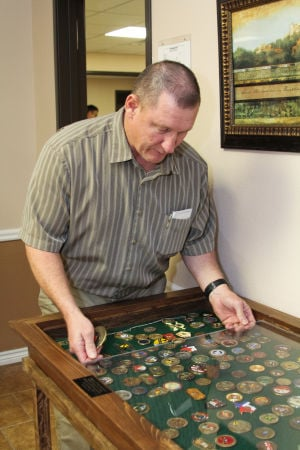 Coins (5): Dale Cowan, director of the Masters Club at North Side Baptist Church, looks at coins collected as part of the church's children's program. Cowan said the coin collection started in 2010 as a way for the children to learn more about God and their country. - Photo by Jodi Perry
