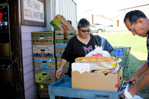 My Brother's House Food Pantry: Mrs. Hernandez watches as her husband pulls a cart of food they received at My Brother's House food pantry Tuesday, Nov. 19, 2013. - Jodi Perry
