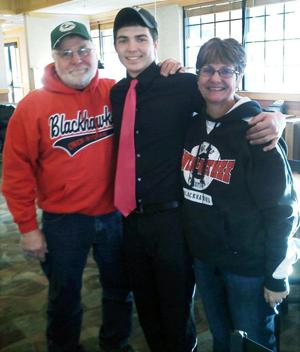 <p>STATE CHAMPION — Brandon Cwikla of the Owen-Withee Blackhawks, won the Division 7 Football Championship at Camp Randall on November 20. He is the son of Tracy Renderman and Otto Cwikla of Owen-Withee as well as the grandson of Dave and Karen Kmosena of Ladysmith who are pictured here with him.</p>