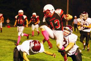 <p>Bruce senior running back Mitchell Heintz gets up and over a Birchwood defender during their homecoming game on Friday night.</p><p></p>