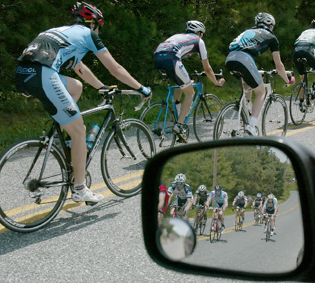 Cyclists are seen coming and going as bikers prepare to climb the hill