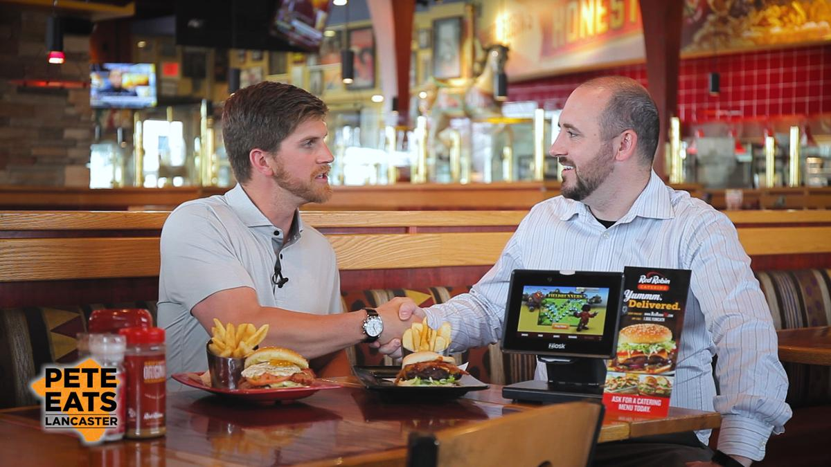 LancasterOnline host Pete Andrelczyk and general manager Cassidy Bailey shake hands, seated at a restaurant table with burger plates and tabletop tablet in front of them
