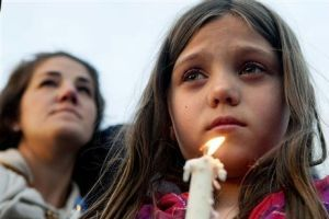 <p>Maya Averill, 9, attends a candlelight vigil for Sgt. Greg Moore, a 16-year veteran of the Coeur d'Alene Police Department who was shot after checking on a suspicious person in a neighborhood, Tuesday, May 5, 2015, in northwest Coeur d'Alene, Idaho. The northern Idaho police officer shot by a man who stole his patrol car died of his injuries Tuesday evening, police said.</p>