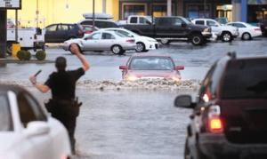 <p>A Lewiston Police Department officer tries to keep a car from driving into the flooded parking lot Monday evening between the Red Lion Hotel and McDonald's on 21st Street in Lewiston. Flooding was reported throughout the Lewiston-Clarkston Valley.</p>