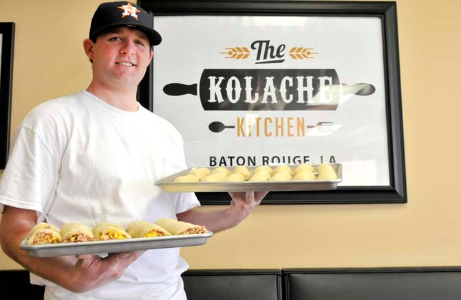kolache kitchen owner will edwards poses with trays of prepared