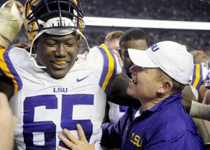 <p>LSU sophomore offensive tackle Jerald Hawkins (65) smiles with head coach Les Miles after the Tigers' 23-17 victory on Thursday, Nov.27, 2014 in Kyle field.</p>
