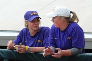 <p>LSU seniors utilities Dylan Supak (11) and Kailey McCasland (33) in the dugout on March 25, 2015 at Tiger Park.</p>