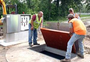 Street Commissioner Bob Nicko prepares to close the lid on the lift station project in Aitkin City Park.