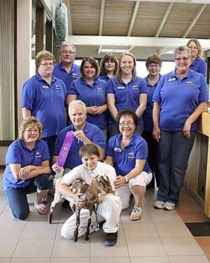 Security State Bank staff poses with Alaina Chute, her goat and the blue ribbon the pair won at the Aitkin County Fair.