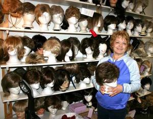 Jeanie Thompson with some of the more than 300 wigs of every size, color and style that fill the shelves lining the walls of Ruth's Free Wig Closet.