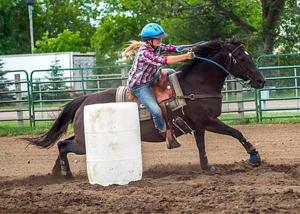 Madison Slette maneuvers barrels in an Aitkin County 4-H horse competition.