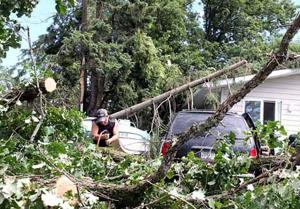 Tyler Hamilton saws away at one of the many large trees that fell on Hill City properties following a severe storm that swept through the area in the early morning hours of July 21.