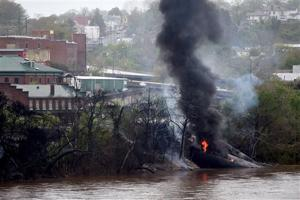 File photo In this April 30, 2014, file photo, firefighters and rescue personnel work along the tracks where CSX tanker cars carrying crude oil derailed and caught fire along the James River in Lynchburg.