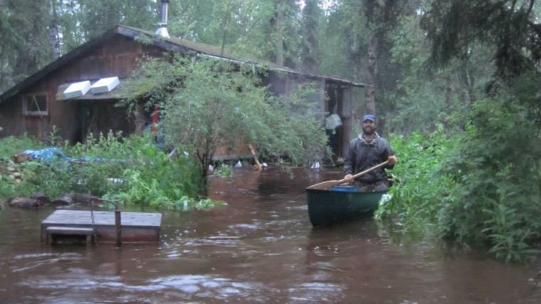 <p>David Jonas paddles a canoe in Goldstream Valley after bringing a skiff up from the Tanana River, where he had traveled to secure his cabin Wednesday night. Photo courtesy Amy Marsh.</p>