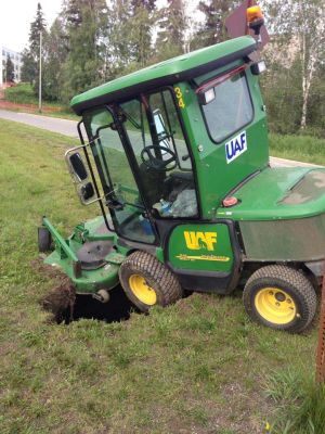 <p>A University of Alaska Fairbanks lawnmower gets stuck in a sinkhole on campus Thursday morning, July 10, 2014.</p>