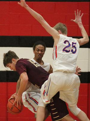 <p>Logan View/Scribner-Snyder's Michael Broussard (12) and Ben Moxness (25) trap Marcus Hegy of Lyons-Decatur Northeast as part of a triangle-and-two defense in the fourth quarter Friday at Scribner. The Raiders edged the Class D No. 5 Cougars 43-41.</p>