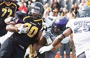 <p>Alex Kline of Wayne State College is brought down by Matthew Young (7) and Carter Ahlers (hidden) of the University of Sioux Falls during Saturday afternoon's game in Wayne.</p>