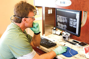 <p>Flintstone dentist Kenneth Pilgrim checks dental X-rays on a computer monitor. (Messenger photo/Matt Ledger)</p>