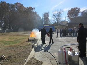 <p>Calhoun Fire Department Lt. Burton Fox teaches, Gordon Central High School 10th-grader Molly Peeler how to use a fire extinguisher Wednesday, November 19, 2014, as Lt. Tim Duvall and classmates look on.</p>
