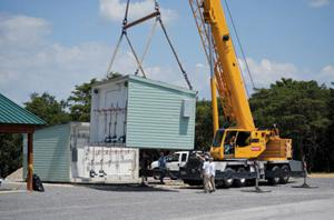 <p>SAFE ROOM GOING IN. Pictured above are crews installing the new safe room at Cherokee Rock Village which arrived in two parts. Brian McKinney with McKinney Construction said the new safe room will accommodate up to 60 campers and can sustain winds of up to 210 miles per hour. The building has four showers and lavatories.</p>