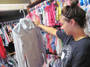 <p>Amber Tidwell arranges new arrivals at Kathy's Korner, a new Rockmart business.</p>