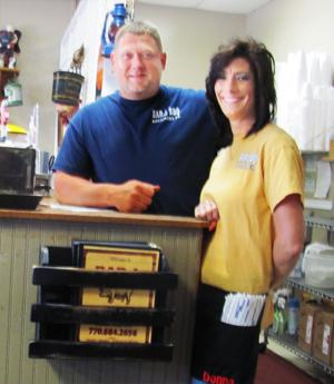 <p>Owner Jeff Dunn gives directions to Donna Lee, lead server, before the crowd arrives for dinner at Bar-L-Bar-B-Que in Rockmart.</p>