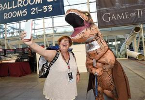"<p>Inger Utke, left, takes a selfie with Edwin Galarza, dressed as a ""Star Wars"" themed dinosaur, during Preview Night at Comic-Con International held at the San Diego Convention Center, Wednesday, July 20, 2016, in San Diego. (Photo by Denis Poroy/Invision/AP)</p>"