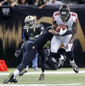 <p>Atlanta Falcons wide receiver Julio Jones (11) is tackled by New Orleans Saints defensive back Pierre Warren (42) in the second half of an NFL football game in New Orleans, Sunday, Dec. 21, 2014. (AP Photo/Bill Haber)</p>
