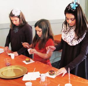 "<p>Gracie Benefield, Emma Watkins and Emma Beck, decorate cupcakes during the ""Cupcakes and Carols for Kids"" program.</p>"
