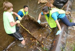 <p>Rome Middle School students drag a shopping cart out of Silver Creek during the Coosa River Basin Initiative's Etowah River Cleansweep on Sept. 17. The project, which included several community groups, cleaned about 55 miles of the Etowah and Coosa rivers as well as Silver Creek.</p>