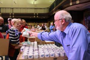 <p>First Presbyterian Church pastor Jeff Chadwick hands his grandson Dawson Chadwick, 2, of Rome, a bag of beans to be put in a box for an in-need Floyd County family on Sunday. (Carolyn Grindrod, RN-T)</p>