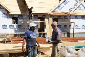 <p>Job foreman Abraham Rodriguez (left) speaks with Martin Duke, director of technical services for the Northwest Georgia Housing Authority, outside a two-bedroom home under construction in the Joe Wright Village gated public housing community in North Rome. (Doug Walker, RN-T)</p>