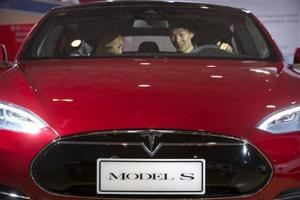 """<p><span id=""""_oneup"""" style=""""font-size: 12px;"""">FILE - In this Monday, April 25, 2016, file photo, a man sits behind the steering wheel of a Tesla Model S electric car on display at the Beijing International Automotive Exhibition in Beijing. Federal officials say the driver of a Tesla S sports car using the vehicle's """"autopilot"""" automated driving system has been killed in a collision with a truck, the first U.S. self-driving car fatality. The National Highway Traffic Safety Administration said preliminary reports indicate the crash occurred when a tractor-trailer made a left turn in front of the Tesla at a highway intersection. NHTSA said the Tesla driver died due to injuries sustained in the crash, which took place on May 7 in Williston, Fla. (AP Photo/Mark Schiefelbein, File)</span>t</p>"""