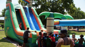 <p>Children line up for the water slide Saturday at Banty Jones Park during a community gathering hosted by the Members Only Civic Club. (Doug Walker, RN-T)</p>