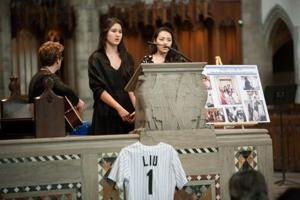 <p>Genevieve Liu (center, at podium) sings at a memorial service for her father in Chicago. Photo credit: Jamie Manley/Chicago Maroon</p>
