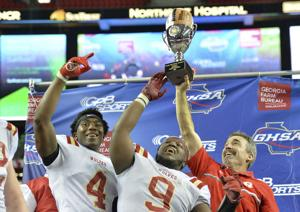 <p>Rome head coach John Reid (right) celebrates the Wolves' win in the Class 5A state championship game Friday night with players Jaylen Griffin (4) and Malik Davis (9). (Hyosub Shin/Atlanta Journal-Constitution via AP)</p>