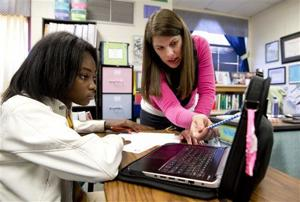 <p>In this Nov. 20, 2014 photo, eight grader Aklya Thomas and teacher Faren Fransworth use a digital textbook to during a math class at Burney Harris Lyons Middle School in Athens Ga. Georgia schools will use only digital textbooks within the next six years under a proposal one state lawmaker has planned for the 2015 session. (AP Photo/John Bazemore)</p>