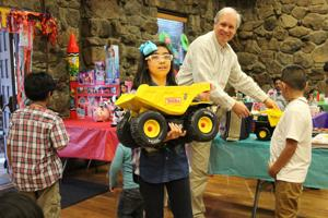 <p>Heidi Aguilar (center), 11, walks away with a Tonka truck raffle prize she received from Sam Baltzer (standing back) during the Three Kings Day celebration at the Rome Civic Center on Saturday, Jan. 14, 2017. (Valeria Rincon Fuentes / RN-T.com )</p>