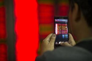 <p>A Chinese investor takes a smartphone photo of electronic displays showing stock prices in a brokerage house in Beijing, Friday, Jan. 8, 2016. Chinese stocks were volatile Friday and other Asian markets rebounded after a plunge in Chinese prices rattled global markets. (AP Photo/Mark Schiefelbein)</p>