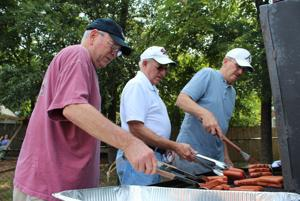 <p>Jim Williams, (from left), Scottie Edwards and Bill Franssen make hot dogs for the group at water day at Second Avenue United Methodist Church. The men were making 200 hot dogs for the crowd, they said. (Kristina Wilder / RN-T.com)</p>