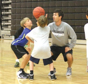 <p>Campers Cole Spear (left) and Jacob Beamer (center) wait for the jump ball from Calhoun assistant coach Brock Holley. (Tasha Bunch, CalhounTimes.com)</p>