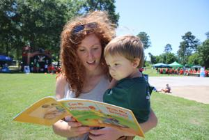 <p>Lindsay Runne reads to her son Isaiah Runne after they picked out a book together at the Summer Feeding event at Ridge Ferry Park. (Kristina Wilder / RN-T.com)</p>