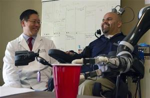 <p>In this April 14, 2015 photo provided by the California Institute of Technology, Dr. Charles Y. Liu, left, a neurosurgeon at the University of Southern California, laughs with patient Erik Sorto in Pasadena, Calif. Liu led a team of doctors that implanted tiny chips into Sorto's brain in 2013 to allow him to control a robotic arm using his thoughts. It's the latest attempt at creating mind-controlled prosthetics to help disabled people gain more independence. (Lance Hayashida/Caltech via AP)</p>