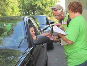 <p>Volunteers assist recipient during recent food distribution.</p>
