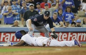 <p>Los Angeles Dodgers' Yasiel Puig, bottom, safely takes third base after hitting a triple as Atlanta Braves third baseman Chris Johnson watches during the fifth inning of a baseball game on Tuesday, July 29, 2014, in Los Angeles. (AP Photo/Jae C. Hong)</p>