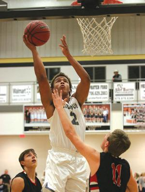 <p>Calhoun's Kaelan Riley (center) goes up for a shot for two of his 24 points during a game this past season against Sonoraville. Riley passed the 1,000-point mark for his career in the game. (Dana Woodard, For the Calhoun Times)</p>